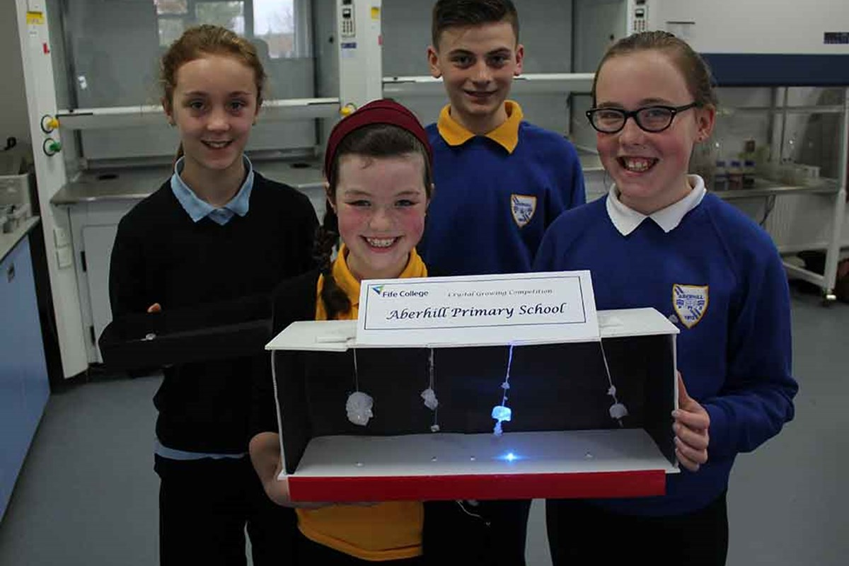 Four school pupils holding box with hanging crystals